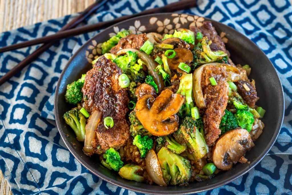 Top down view of a black bowl filled with stir fried beef, broccoli, mushrooms, and onions over a blue checked napkin. A set of chop sticks sit in the background.
