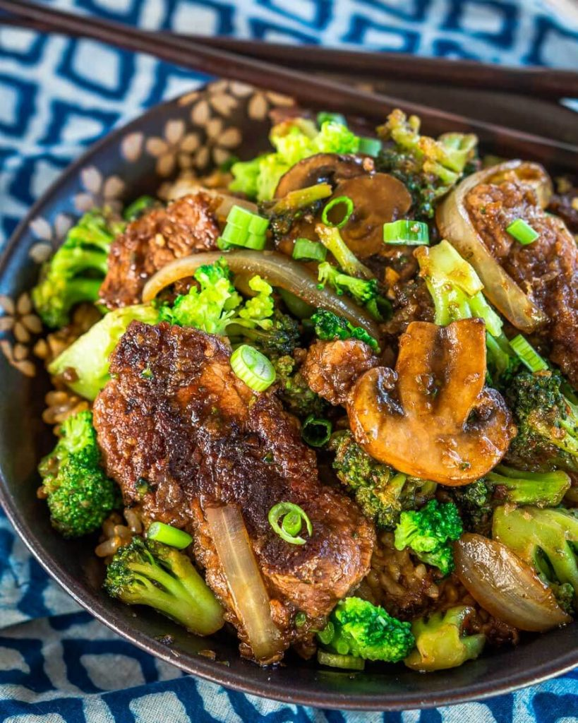 Close up top down view of a black bowl filled with Beef and Broccoli Stir Fry over a blue checked napkin. A set of chopsticks sits on the back of the bowl.