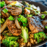Side view of a black bowl filled with Beef and Broccoli Stir Fry over brown rice. The recipe title runs across the top for Pinterest.