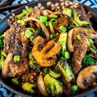 Angled view of a black bowl filled with Beef Broccoli Stir Fry over a blue checked napkin. A set of chop sticks sit in the background.