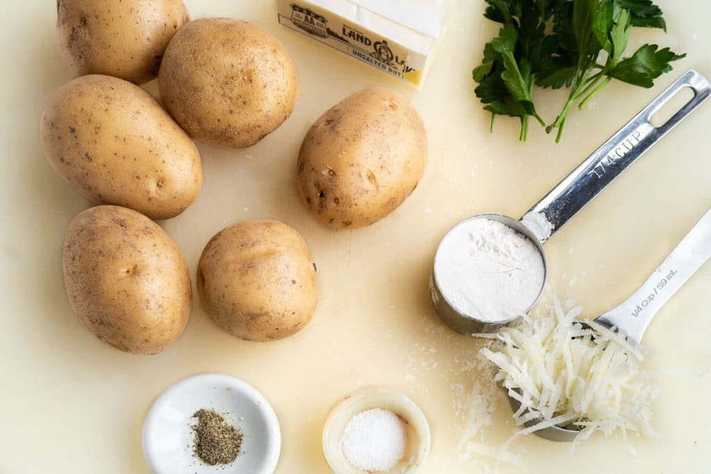 A cutting board holding potatoes, flour, parmesan, butter, parsley, salt and pepper
