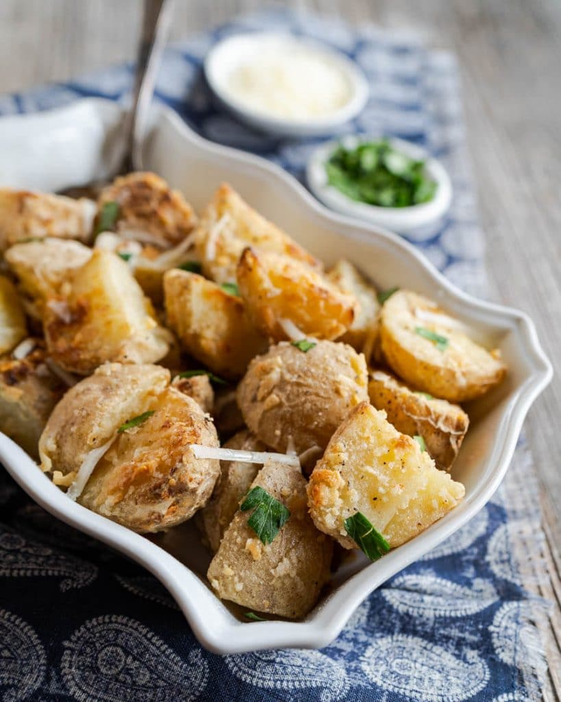 Side view of cheese crusted potatoes garnished with chopped parsley.