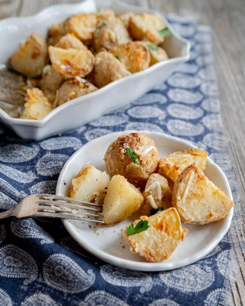 A plate of parmesan crusted roasted potatoes with one cut in half. A baking dish filled with potatoes sits in the background.