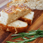 Side view of sliced Focaccia bread topped with cheese and herbs on a wooden cutting board. Fresh rosemary sits in the front.