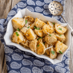 Closeup angle view of crispy parmesan crusted potatoes in a baking dish with a serving spoon sitting to the back.