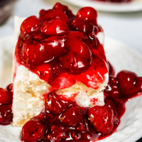 3/4 angle of a slice of meringue dessert topped with a cherry raspberry filing.