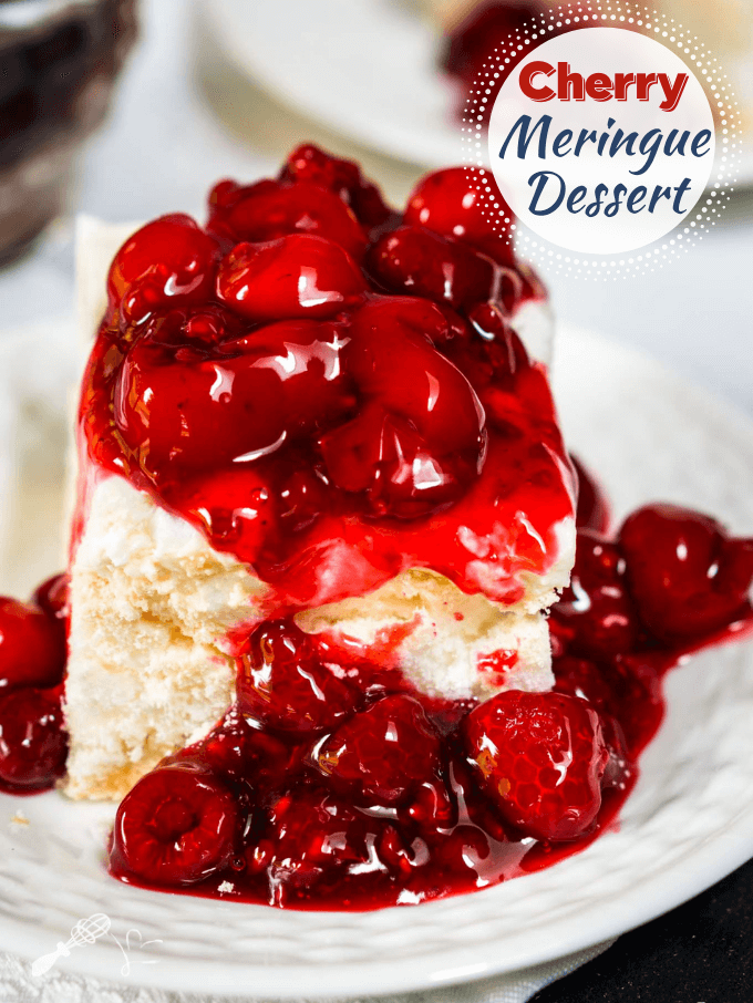 Table view of a white plate holding a piece of meringue dessert topped with a cherry raspberry sauce.