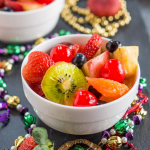 A white bowl filled with chunks of fresh fruit and surrounded by colorful beads.