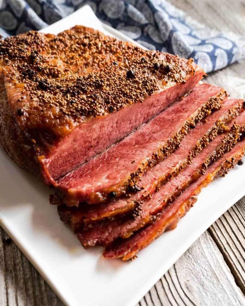 3/4 side view of a baked corned beef brisket that's been sliced and sitting on a white platter.