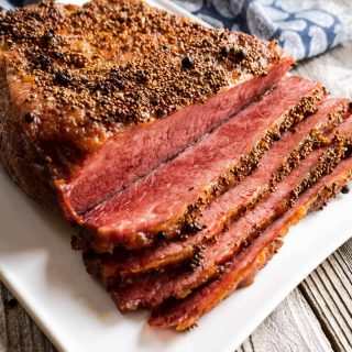Top down of a baked and sliced corned beef brisket sitting on a white plate.