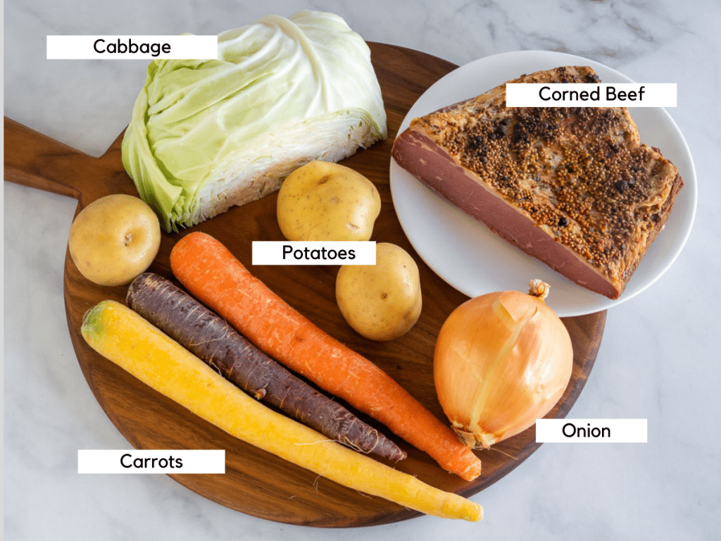 Carrots, potatoes, onion, cabbage, and corned beef brisket on a wooden cutting board.