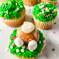 Cupcakes decorated with a grass tip with a bunny butt made from a donut hole sticking out.