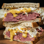 Corned Beef sandwich overloaded with sliced corned beef, mustard sauce and a cabbage slaw.