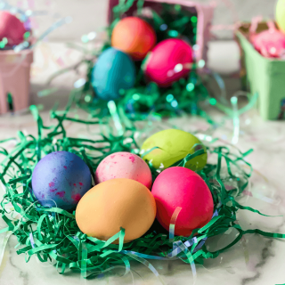 Tableview photo of dyed Easter Eggs sitting on shredded of green grass with cartons of colored eggs sitting in the background