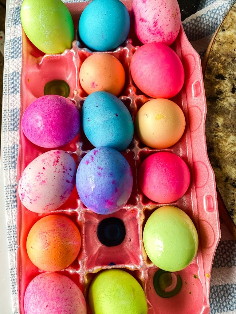 Multi-colored dyed eggs sitting in an egg carton.