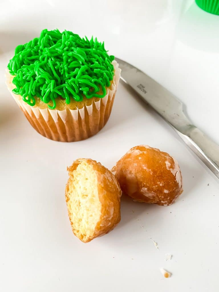A donut hole cut in half to make the bunny's butt and a cupcake piped with grass.