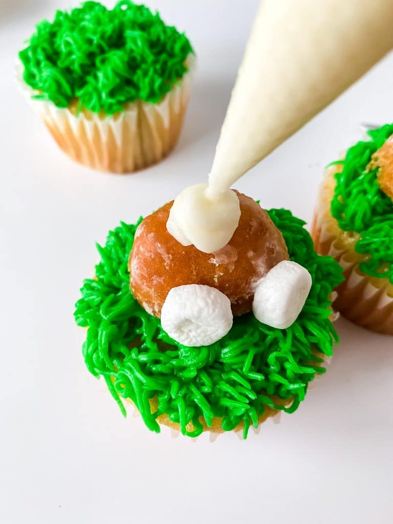 Piping the bunny's tail on a bunny cupcake.