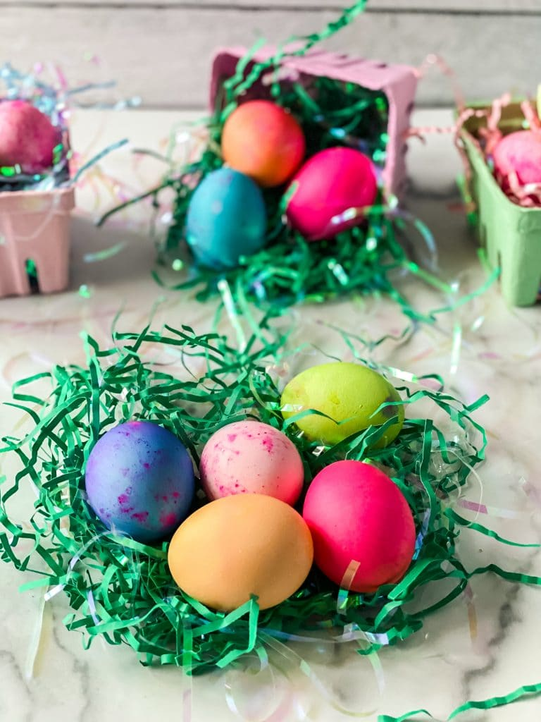 Multi-colored dyed Eggs sitting in shredded green paper