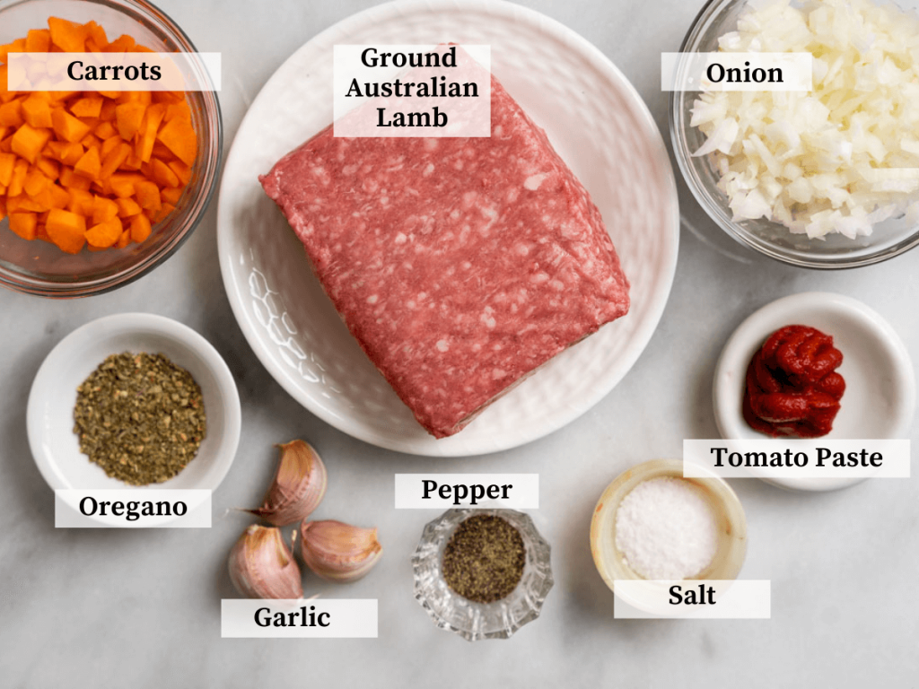 Top down photo of meat sauce ingredients including ground lamb, onion, carrots, tomato paste, garlic, Italian seasoning, salt, and pepper.