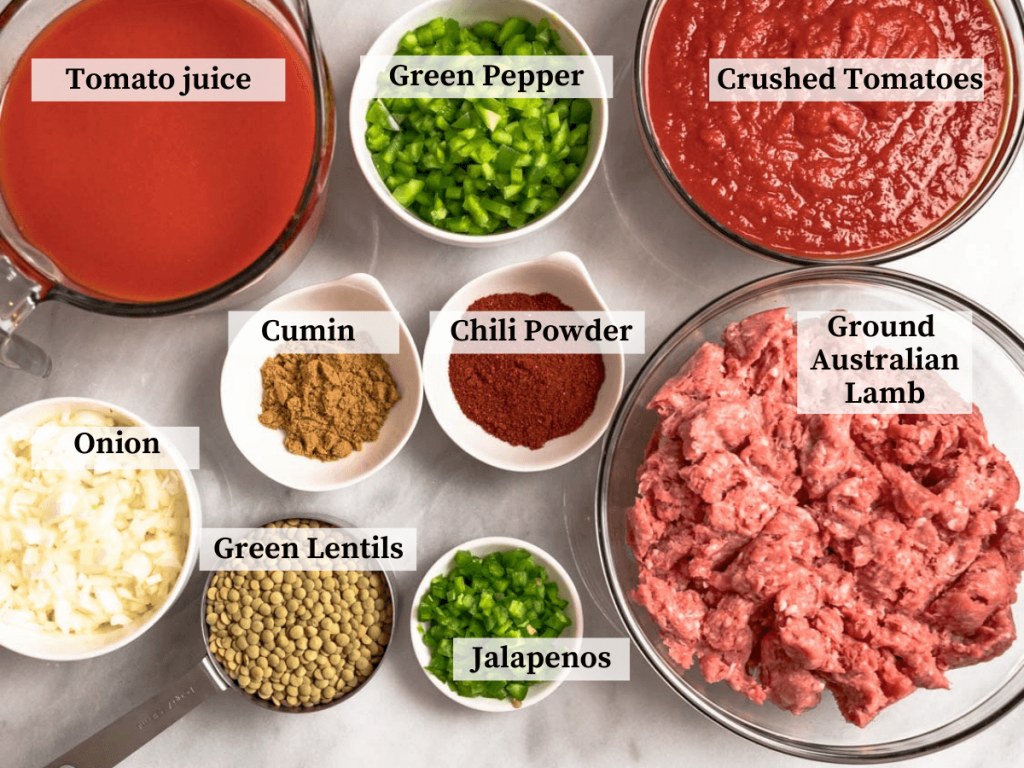 Top down view of ingredients including ground lamb, lentils, jalapenos, onions, green pepper, chili powder, cumin, tomato juice, and crushed tomatoes