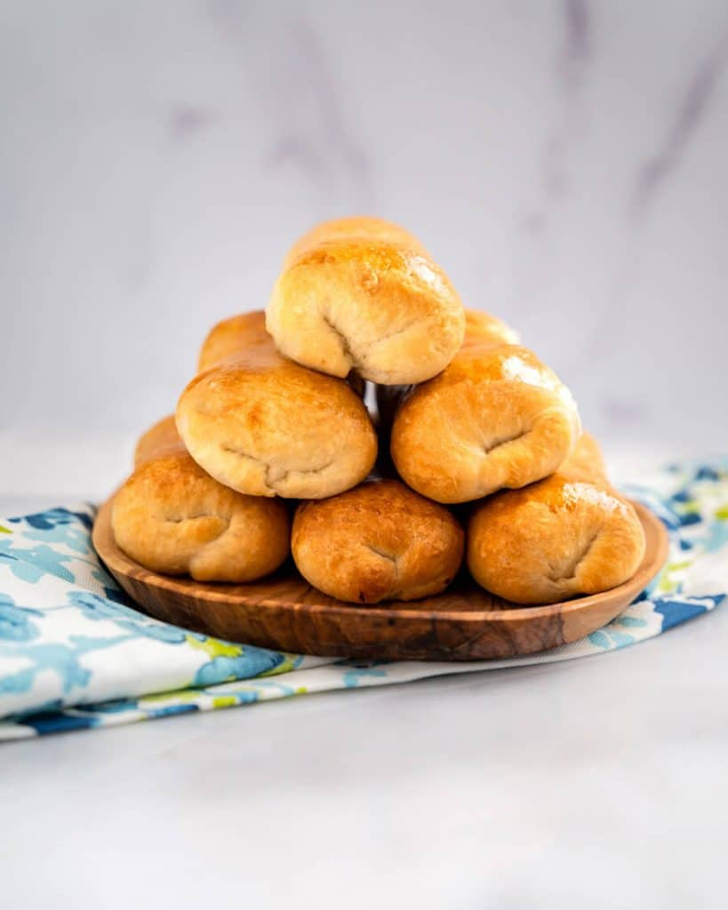 Table view of baked meat-filled buns in a stack of six.