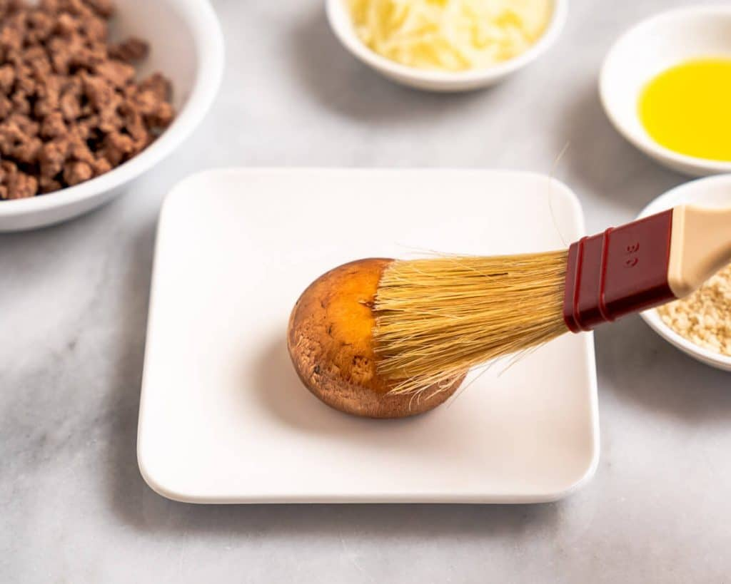 A mushroom being brushed with olive oil.