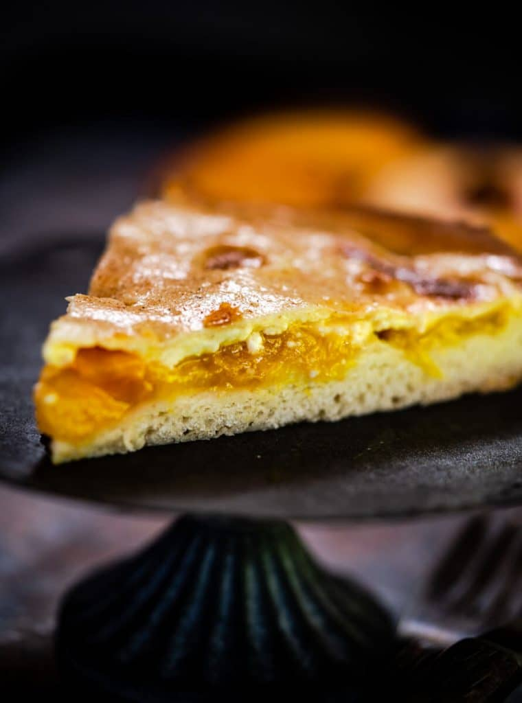 Tableview of a wedge of peach kuchen.