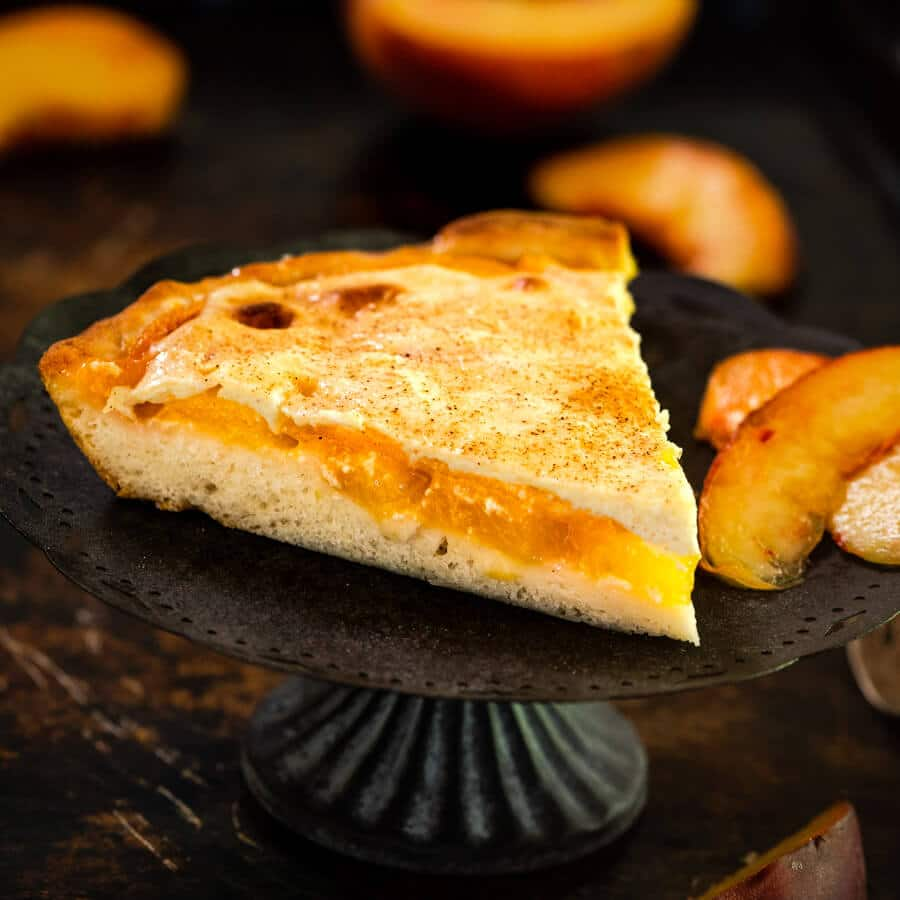 Tableview of a wedge of Peach Kuchen Dessert.