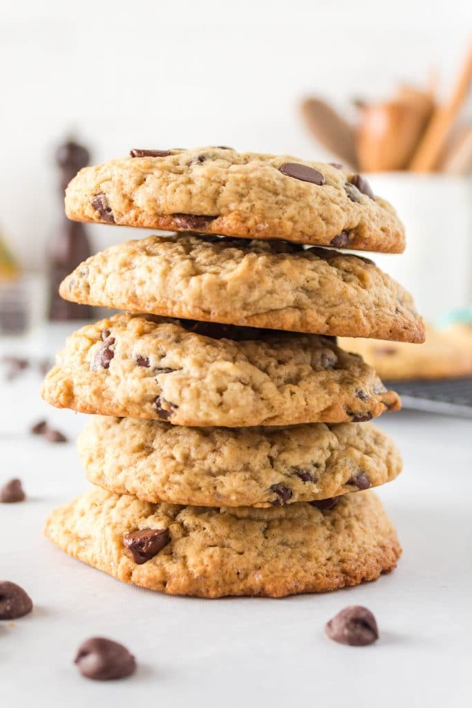 A stack of chocolate chip cookies with chips scattered around the bottom.