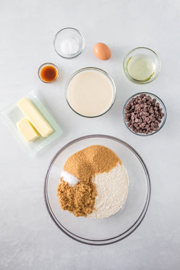 top down view of ingredients used to make sourdough chocolate chip cookies including sourdough starter, flour, sugar, vanilla, butter, baking soda, oil, egg, and salt and chocolate chips