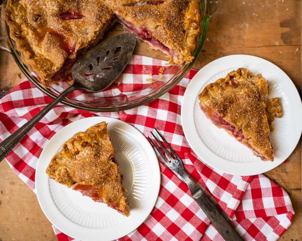 Flay lay photo of two slices of pie on a red checkered napkin with the cut pie in the background.