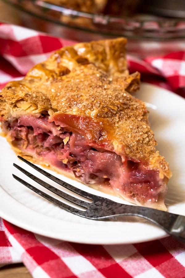 A single slice of a strawberry rhubarb pie recipe on a plate.
