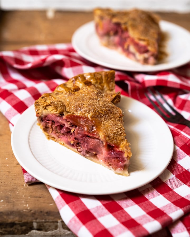 Single slice of strawberry rhubarb pie on a plate with other pieces in the background.