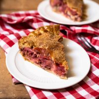 A single slice of a strawberry rhubarb pie recipe on a plate with a second slice in the background.