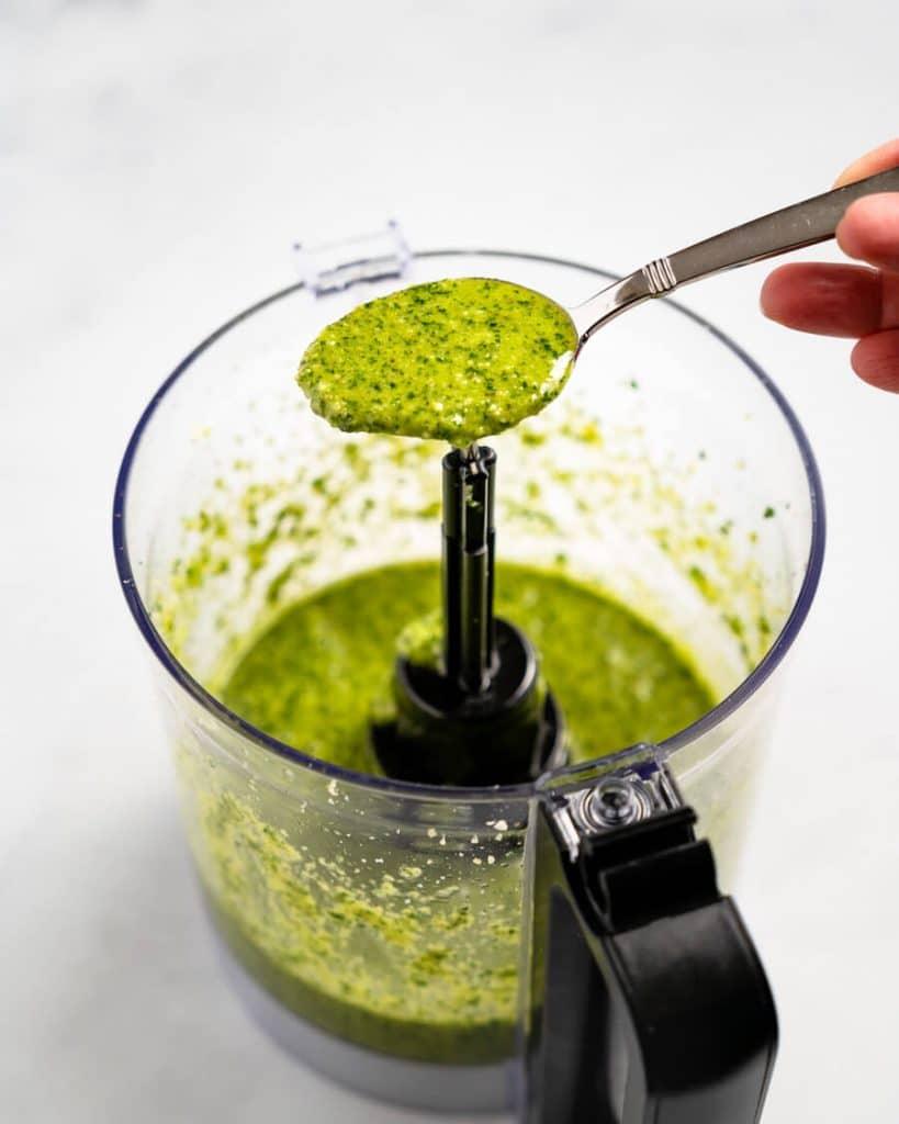 Spoonful of cilantro pesto sitting over a food processor
