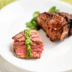Sliced lamb with a drizzle of pesto in front of an uncut lamb chop