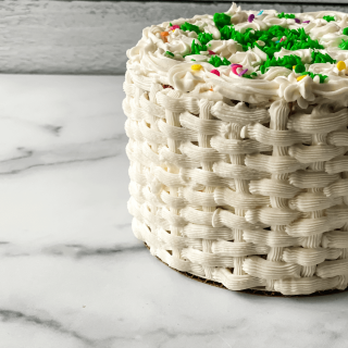 Close-up side view of a decorated Cake with a basket weave design and colorful flowers.