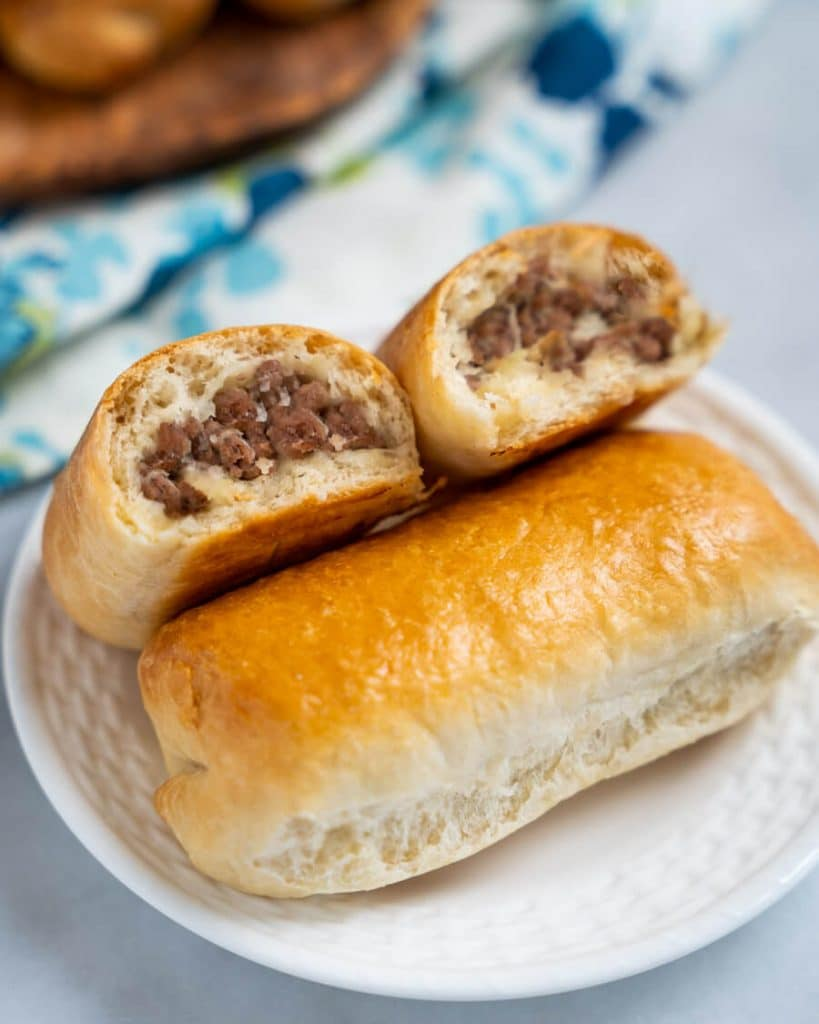 A meat bun cut in half showing cooked meat filling. The halves are leaning against a whole meat bun