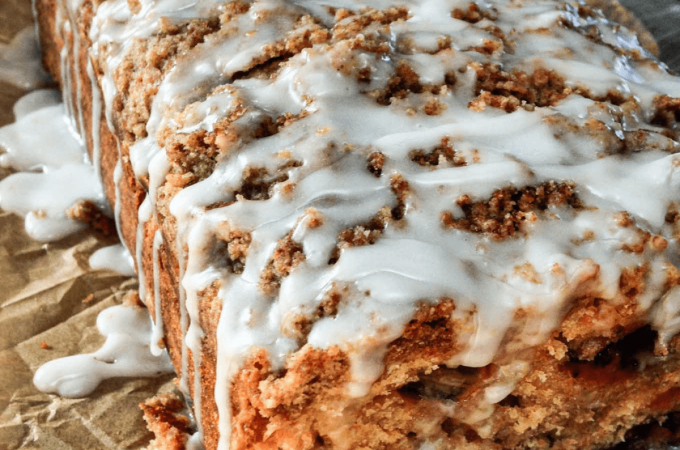 A loaf of strawberry rhubarb quick bread with streusel topping and glazed with icing.