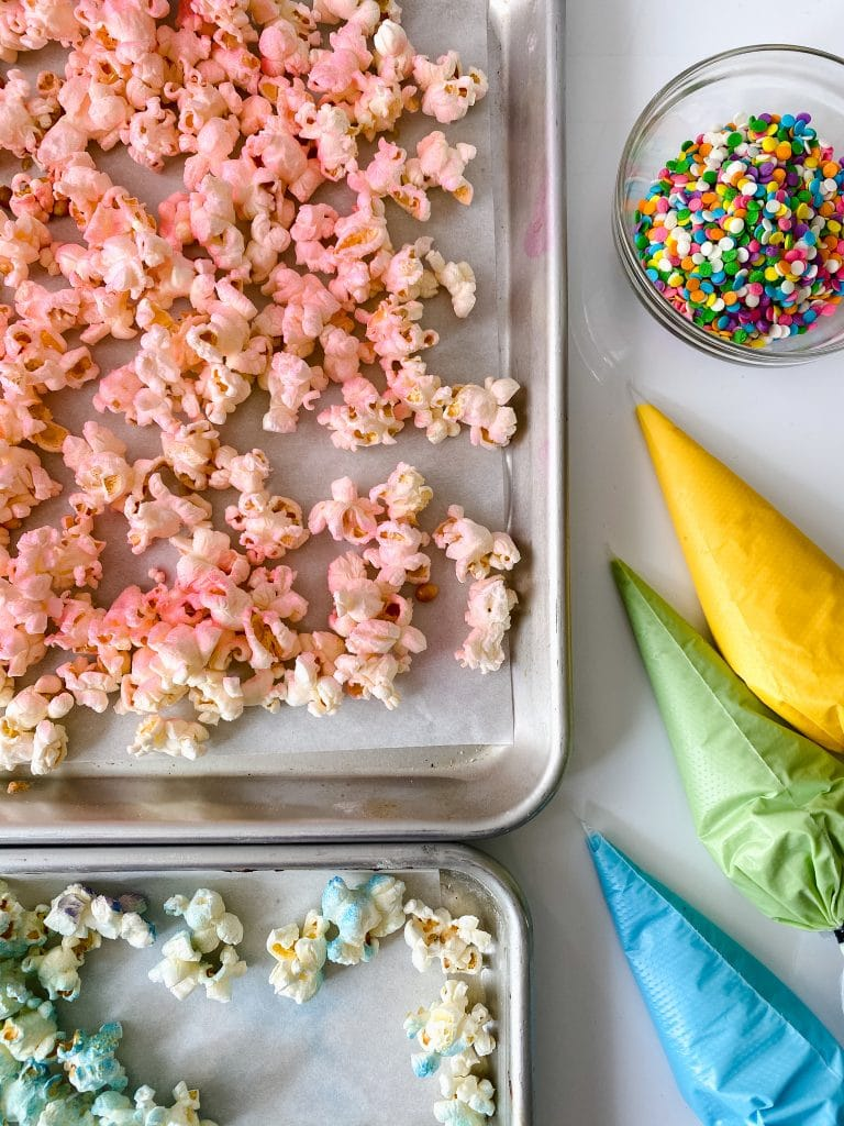 How to make unicorn popcorn. Steps demonstrated include spraying the popcorn pink, piping the chocolate.