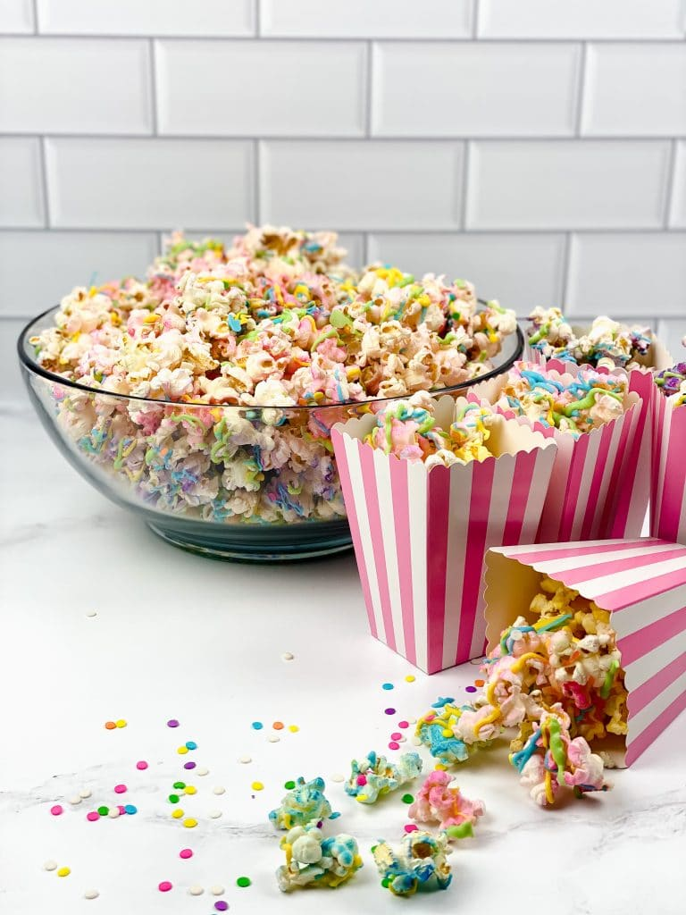 unicorn popcorn in a bowl on the counter with individual servings in pink and white striped single serving popcorn bags in front of a white tiled wall.