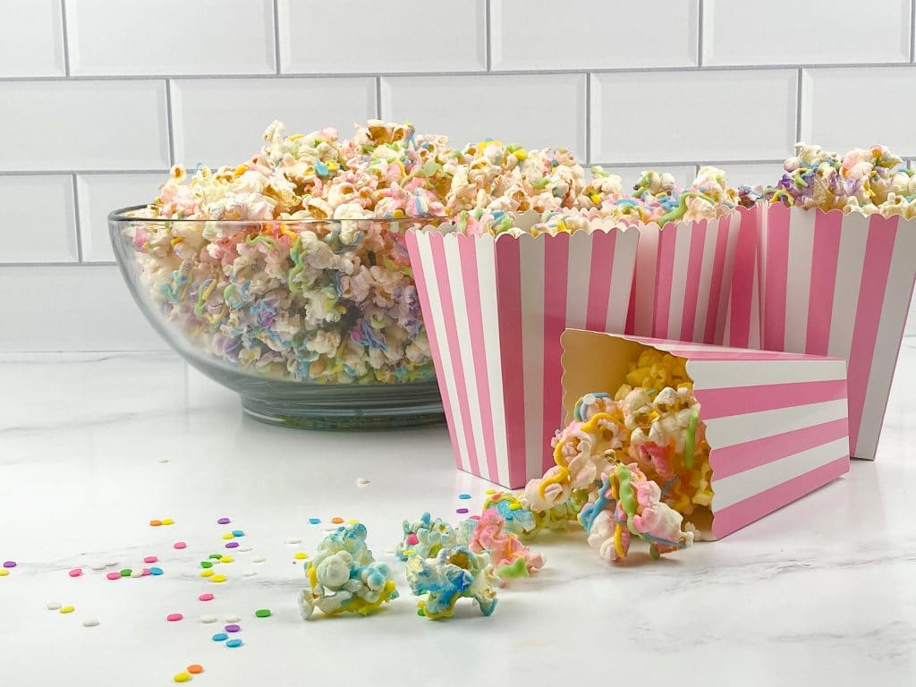 Popcorn boxes filled with multi-colored popcorn with the bowl in the background.