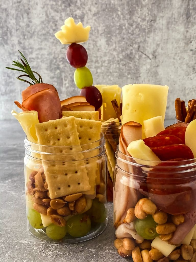 close up of small jars filled with meats, cheeses, crackers, nuts, and grapes