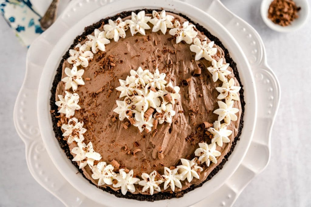 Top down photo of a chocolate pie decorated with whipped cream stars and chocolate shavings