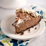 Side angle of a slice of chocolate cheesecake pie sitting on a plate over a multicolored napkin