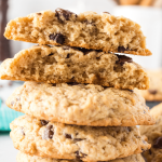 Side view of a stack of chocolate chip cookies with the top cookie broken in half