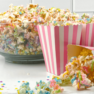 Striped popcorn boxes filled with multi-colored popcorn. The bowl of the popcorn sits in the background.