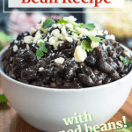 Side view of a bowl of black beans garnished with cilantro and a wedge of lime.