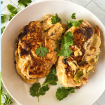 Top down image of two cooked chicken breasts with cheese and peppers over the top and garnished with cilantro.