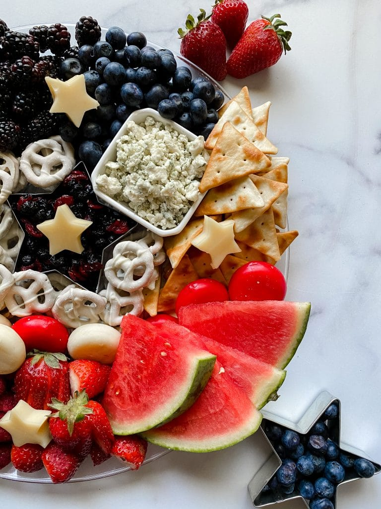 beautiful patriotic charcuterie board with crackers, cheese, and fruit.